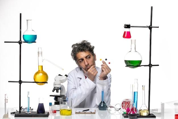 Vooraanzicht mannelijke wetenschapper monsters te houden voor tafel met oplossingen op witte achtergrond coronavirus gezondheidslaboratorium covid