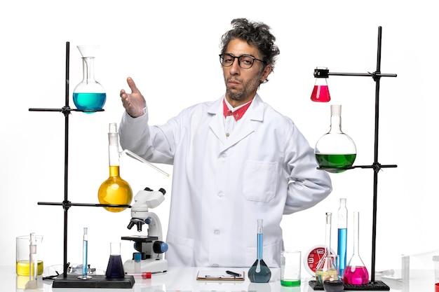 Vooraanzicht mannelijke wetenschapper poseren met oplossingen