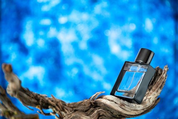 Vooraanzicht mannen parfum op tak verrot hout geïsoleerd op blauwe achtergrond vrije ruimte