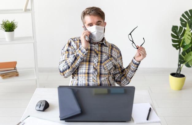 Vooraanzicht mannetje met gezichtsmasker thuis werken