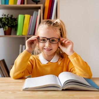 Vooraanzicht meisje met bril lezen