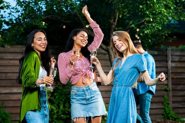 Vooraanzicht meisjes met drankjes dansen