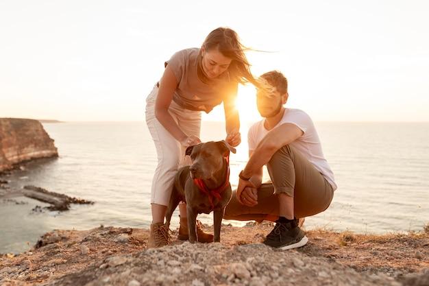 Vooraanzicht mensen spelen met hun hond bij zonsondergang