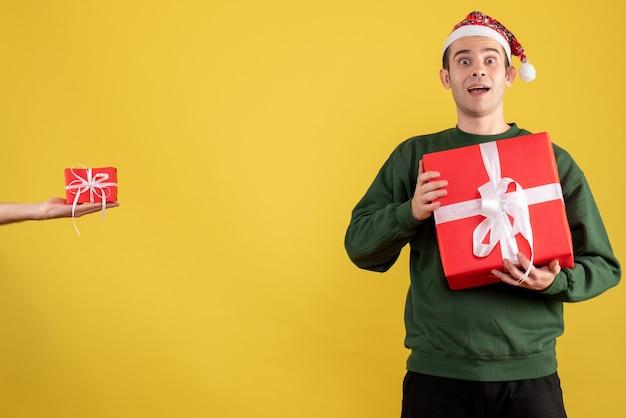 Vooraanzicht met grote ogen jonge man met kerst cadeau het geschenk in vrouwelijke hand op geel