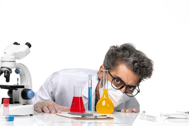 Vooraanzicht middelbare leeftijd wetenschapper in speciaal pak zitten met oplossingen op witte achtergrond mannelijke virus wetenschap covid chemie