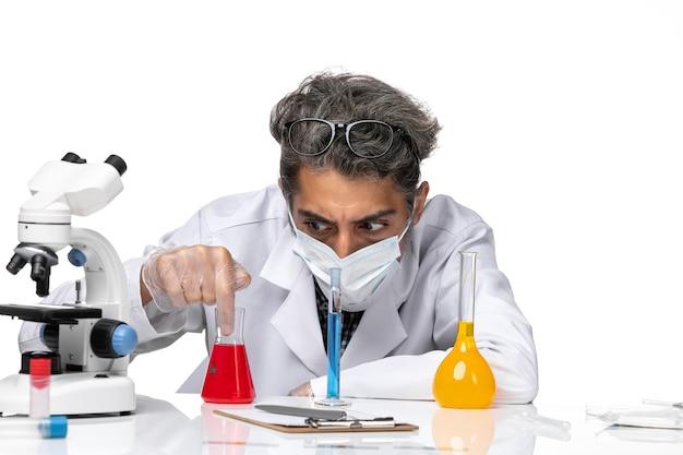 Vooraanzicht middelbare leeftijd wetenschapper in speciaal pak zittend met oplossingen op een wit bureau mannelijke virus wetenschap covid-chemie