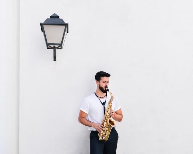 Vooraanzicht middelgrote ontsproten musicus die de saxofoon speelt