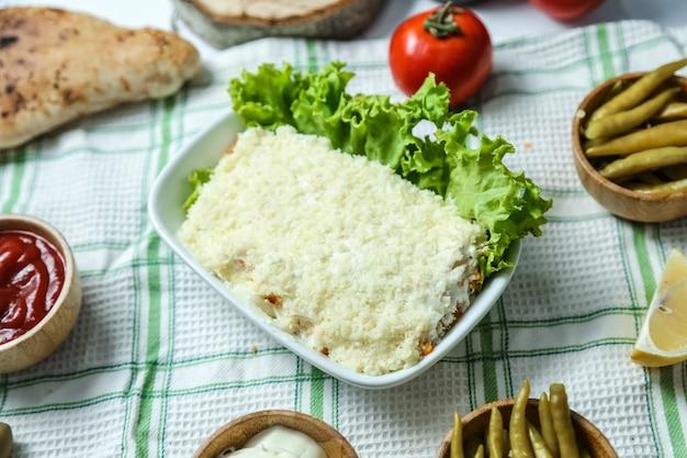 Vooraanzicht mimosa salade met ketchup en mayonaise tomaten en paprika's op tafel