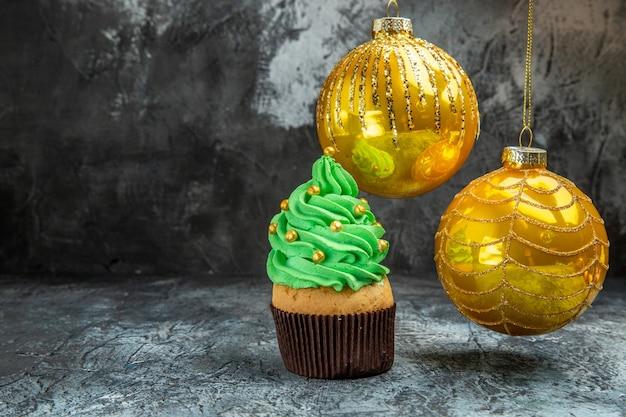 Vooraanzicht mini kleurrijke cupcakes gele kerstboomballen op donkere vrije plaats