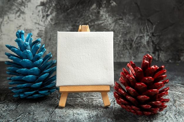 Vooraanzicht mini wit canvas met houten ezel kleurrijke dennenappels op donkere geïsoleerde achtergrond