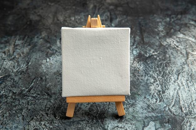 Vooraanzicht mini wit canvas met houten ezel op dark