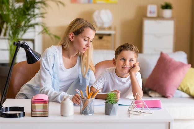 Vooraanzicht moeder en zoon huiswerk binnenshuis