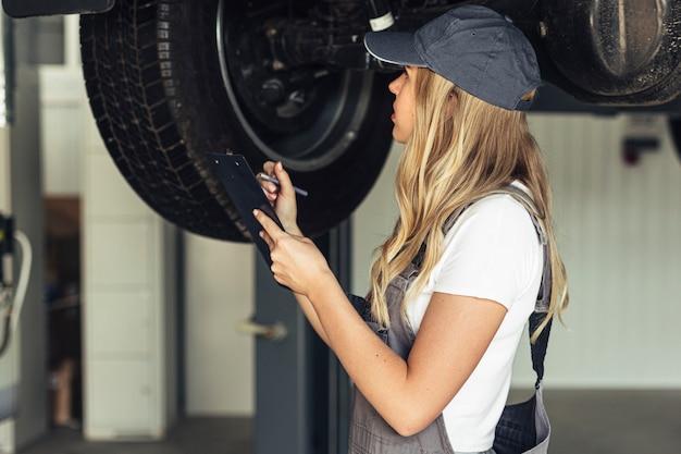 Vooraanzicht monteur vrouwelijke veranderende wielen