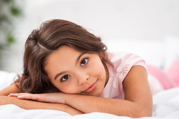 Vooraanzicht mooi meisje gelegd in bed