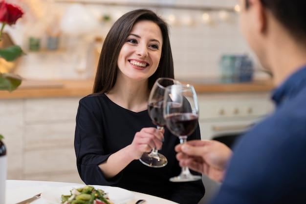 Vooraanzicht mooi paar dat met glazen wijn toejuicht