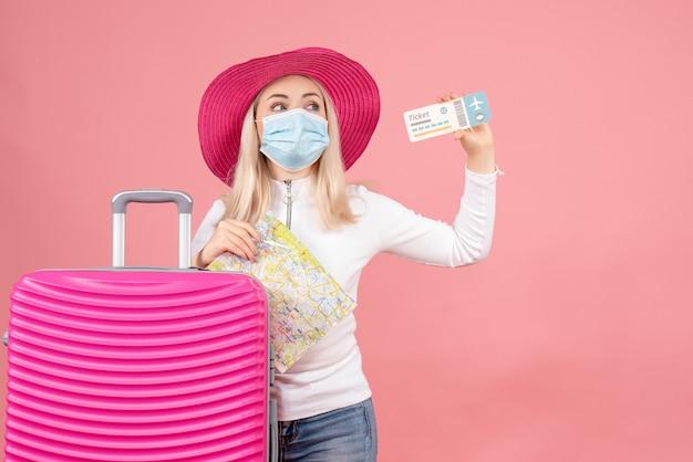 Vooraanzicht mooie blonde vrouw in masker staande in de buurt van het vliegticket van de kofferholding