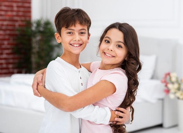 Vooraanzicht mooie broers en zussen knuffelen