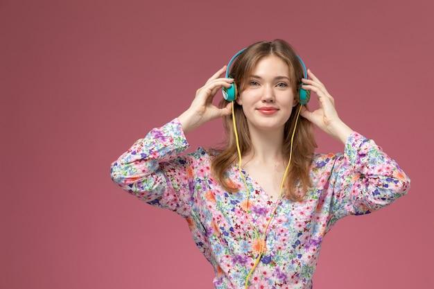 Vooraanzicht mooie dame haar hoofdtelefoon op donker roze muur zetten