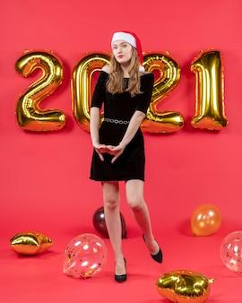 Vooraanzicht mooie dame in zwarte jurk ballonnen op rood
