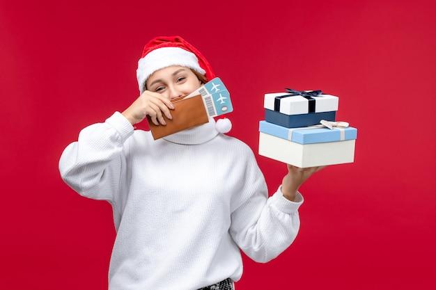 Vooraanzicht mooie dame met kaartjes en cadeautjes op rode achtergrond