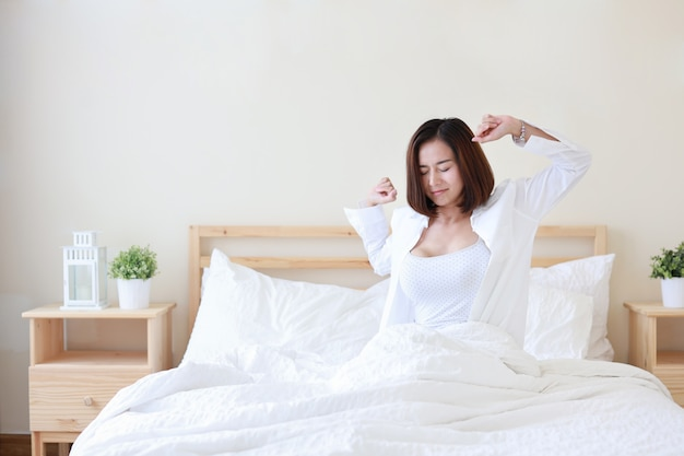 Vooraanzicht mooie en gezonde jonge aziatische vrouw wakker in de ochtend