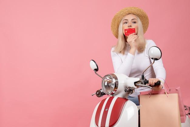 Vooraanzicht mooie jonge dame op bromfiets die haar creditcard kust