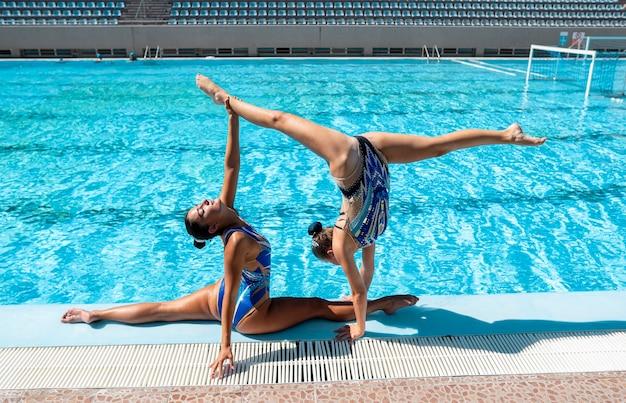 Vooraanzicht mooie meisjes poseren bij het zwembad