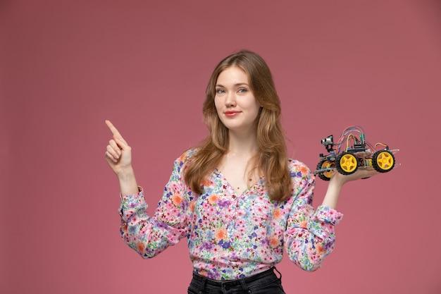 Vooraanzicht mooie vrouw die haar rechterkant met autostuk speelgoed wijst