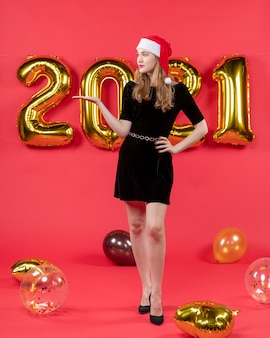 Vooraanzicht mooie vrouw in zwarte jurk ballonnen op rood