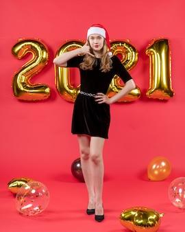Vooraanzicht mooie vrouw in zwarte jurk maken bel me telefoon teken ballonnen op rood