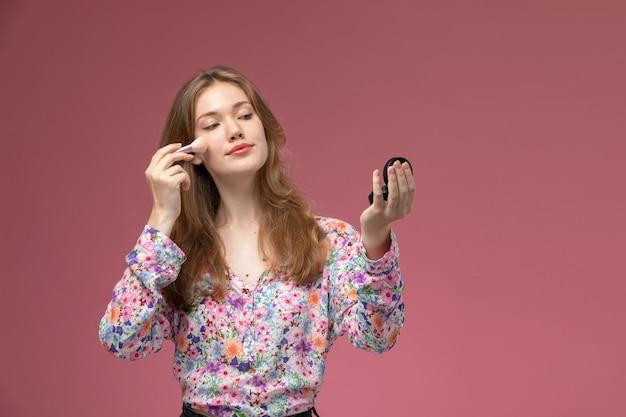 Vooraanzicht mooie vrouw met behulp van cosmetische poederborstel voor haar make-up