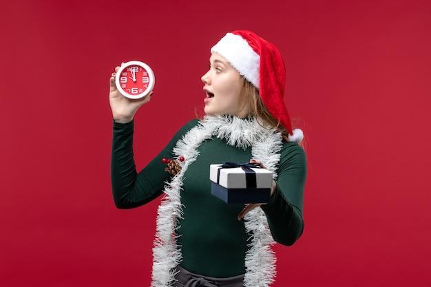 Vooraanzicht mooie vrouw met cadeautjes met klok op rode achtergrond