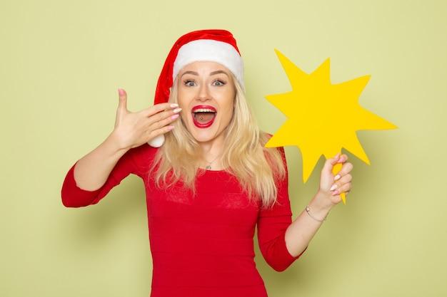 Vooraanzicht mooie vrouw met grote gele figuur op de groene muur kerst emotie sneeuw nieuwjaar kleur vakantie