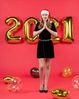 Vooraanzicht mooie vrouw met kerstmuts ballonnen op rood