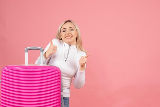Vooraanzicht mooie vrouw met roze koffer duimen opgevend