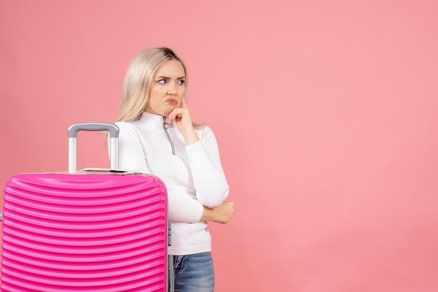 Vooraanzicht mooie vrouw met roze koffer iets na te denken