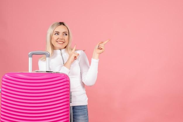Vooraanzicht mooie vrouw met roze koffer naar links wijzend