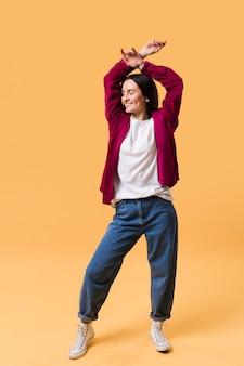 Vooraanzicht mooie vrouw poseren met een oranje achtergrond
