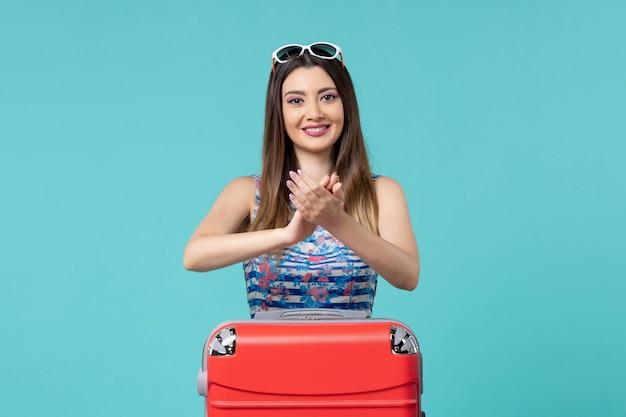 Vooraanzicht mooie vrouw vakantie voorbereiden met rode zak klappen op blauwe ruimte