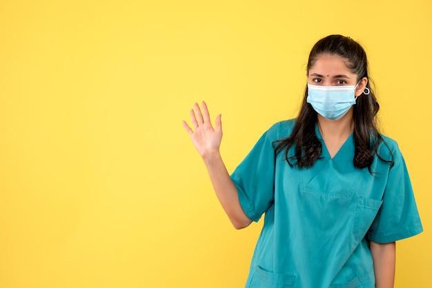 Vooraanzicht mooie vrouwelijke arts in uniform begroet op gele achtergrond