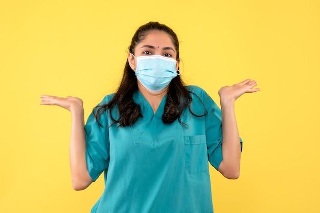 Vooraanzicht mooie vrouwelijke arts in uniform die haar handen opent die zich op gele achtergrond bevinden