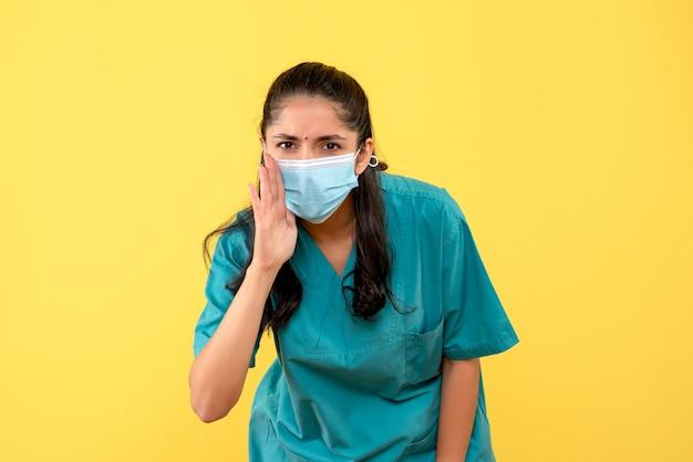 Vooraanzicht mooie vrouwelijke arts in uniform iets vertellen op gele achtergrond