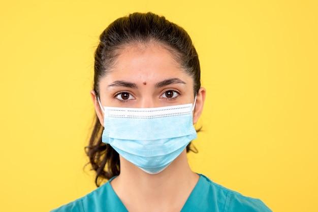 Vooraanzicht mooie vrouwelijke arts met masker staande op gele achtergrond