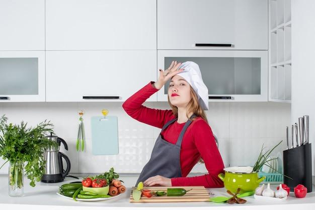 Vooraanzicht mooie vrouwelijke chef-kok in koksmuts die in de keuken staat