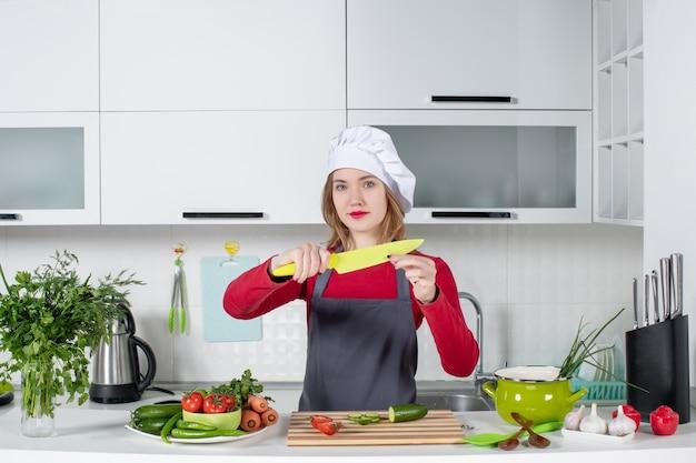 Vooraanzicht mooie vrouwelijke kok in schort die mes omhoog houdt