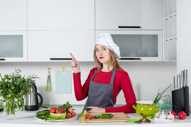 Vooraanzicht mooie vrouwelijke kok in schort die naar links wijst