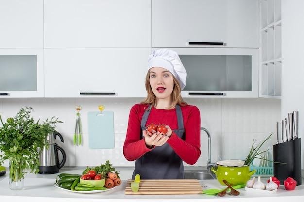 Vooraanzicht mooie vrouwelijke kok in schort die tomaten omhoog houdt