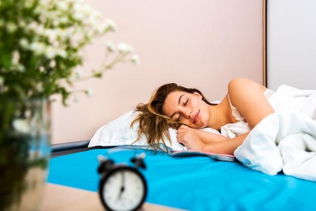 Vooraanzicht mooie vrouwenslaap in bed
