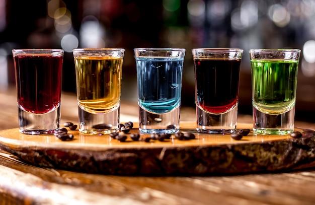 Vooraanzicht multi-gekleurde shots met koffiebonen op een stuk hout