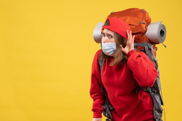 Vooraanzicht nieuwsgierig jong meisje met toeristenrugzak en masker dat naar iets luistert
